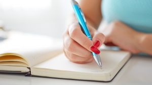 woman writing with a blue pen